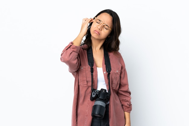 Mulher jovem fotógrafo sobre parede branca com dor de cabeça Foto Premium