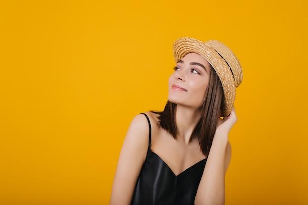 Mulher jovem graciosa no top de seda desfrutando. retrato de uma linda garota tocando seu chapéu de palha. Foto gratuita