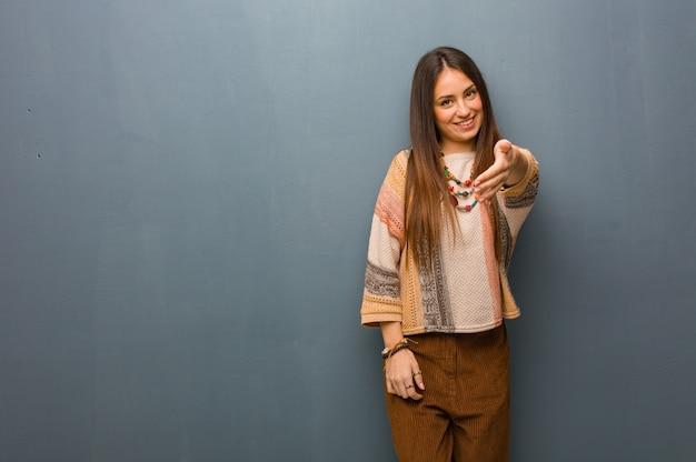 Mulher jovem hippie estendendo a mão para cumprimentar alguém Foto Premium