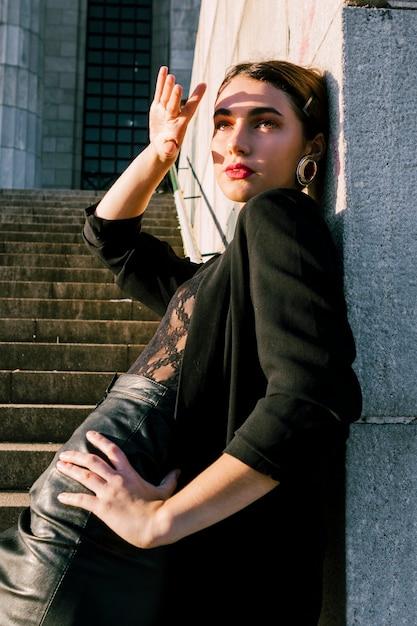 Mulher jovem, inclinar-se, parede, protegendo, dela, olhos, com, mão, de, luz solar Foto gratuita