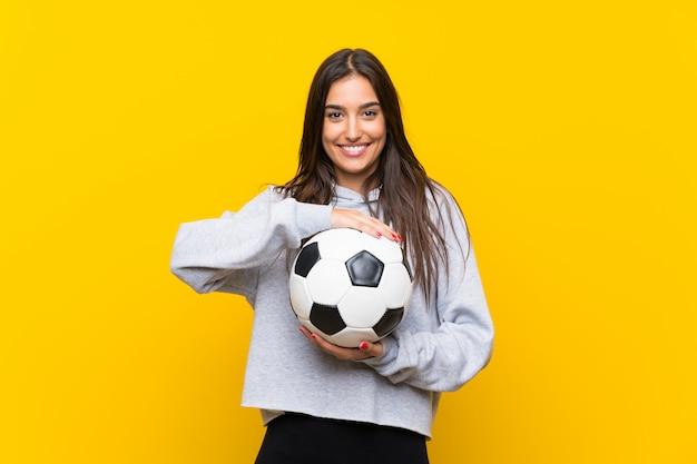 Mulher jovem jogador de futebol isolado parede amarela Foto Premium