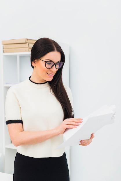 Mulher jovem, leitura, papeis, em, escritório Foto gratuita