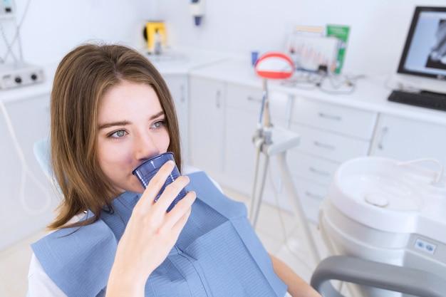 Mulher jovem, levando, água, enquanto, sentando, em, cadeira dental Foto gratuita