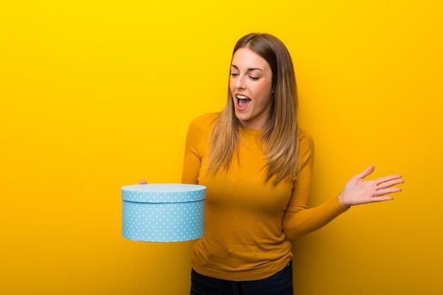 Mulher jovem, ligado, experiência amarela, segurando, caixa presente, em, mãos Foto Premium
