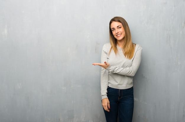 Mulher jovem, ligado, textured, parede, apresentando, um, idéia, enquanto, olhar, sorrindo, direção Foto Premium