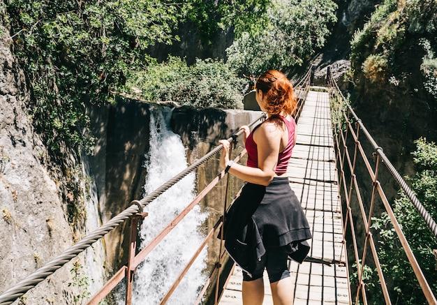 Mulher jovem, ligado, um, ponte suspensão, andar, ligado, a, los cahorros, rota, granada, espanha Foto Premium