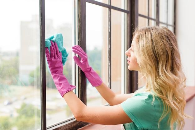 Mulher jovem, limpeza, janela, com, pano, casa Foto gratuita