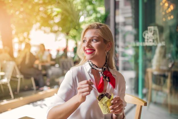 Mulher jovem loira sorridente comendo bolinho de chocolate no suporte de papel Foto gratuita