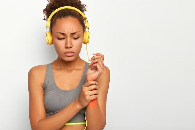 Mulher jovem machucou o pulso, tocando o braço com dor vermelha Foto gratuita