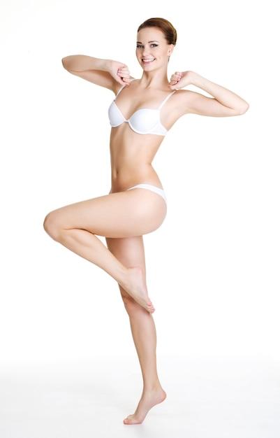 Mulher jovem magro feliz com belo corpo perfeito posando em branco. retrato de corpo inteiro Foto gratuita