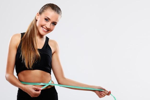 Mulher jovem, medindo cintura Foto gratuita