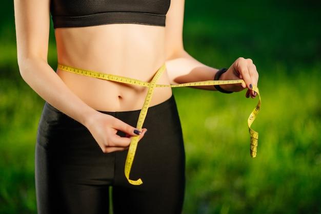 Mulher jovem, medindo, dela, cintura fina, com, um, fita métrica Foto gratuita