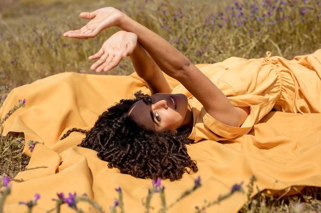 Mulher jovem, mentindo, ligado, pano amarelo, em, natureza Foto gratuita