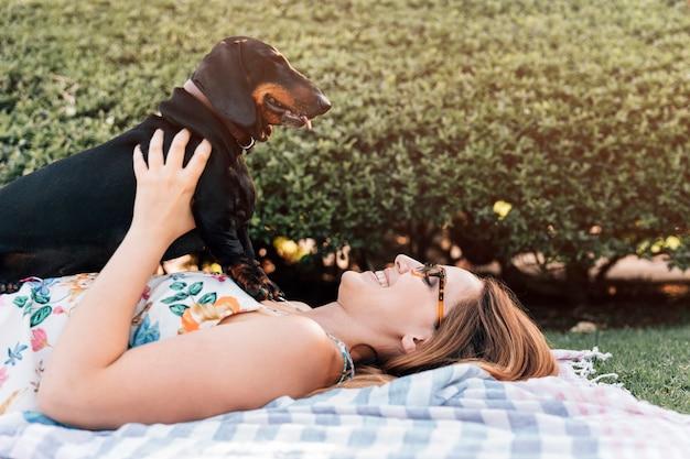 Mulher jovem, mentindo, parque, com, dela, cão Foto gratuita
