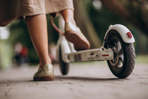 Mulher jovem, montando, scooter, em, pés parque, cima Foto gratuita