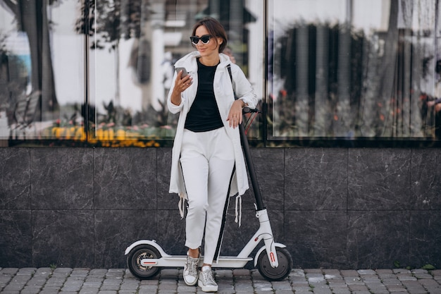 Mulher jovem, montando, scotter, em, cidade, e, usando telefone Foto gratuita