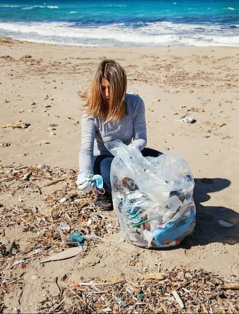 Mulher jovem mostra máscara cirúrgica durante a limpeza da área da praia Foto Premium