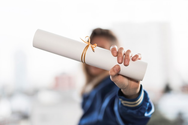 Mulher jovem, mostrando, diploma Foto gratuita