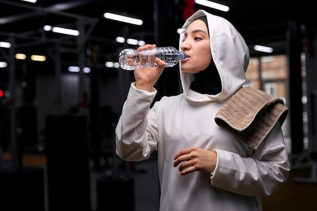 Mulher jovem muçulmana esportes fitness vestida de hijab branco na garrafa de água potável de ginásio, descansar após o treino, exercícios de esporte. retrato Foto Premium