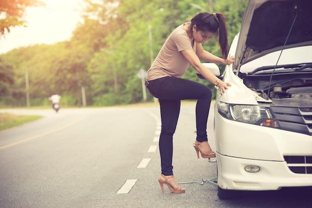 Mulher jovem, mudança, pneu plano, em, campo Foto Premium