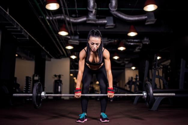 Mulher jovem musculoso fitness fazendo exercícios de levantamento terra pesados no ginásio Foto Premium