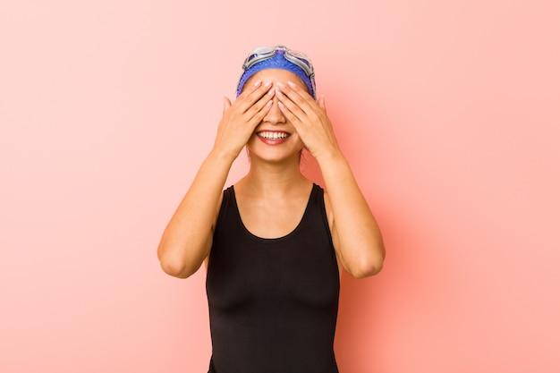 Mulher jovem nadador árabe isolada cobre os olhos com as mãos, sorri amplamente esperando por uma surpresa. Foto Premium