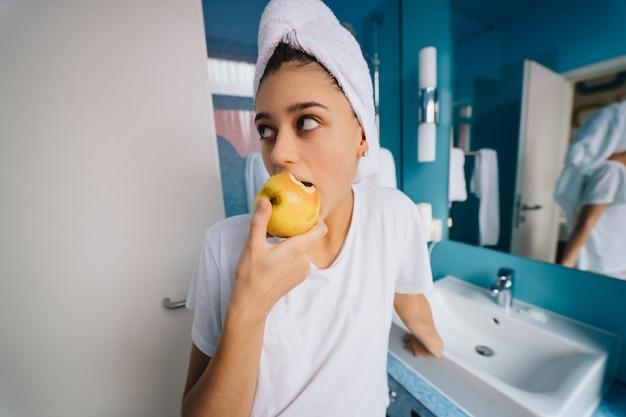 Mulher jovem no banheiro, comendo maçã Foto gratuita