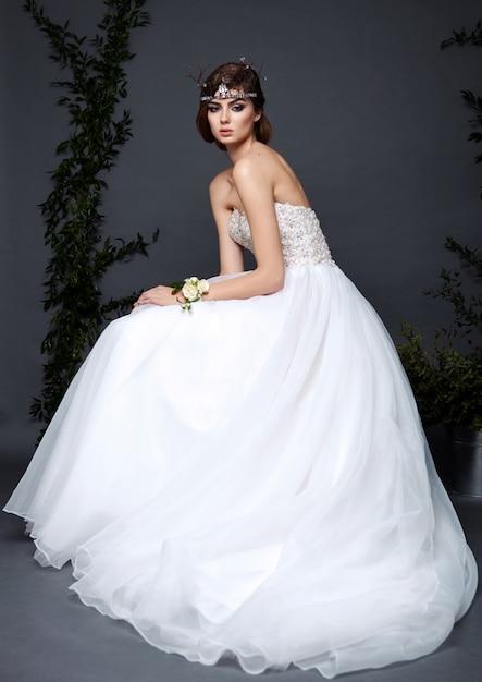 Mulher jovem noiva vestido de noiva no estúdio com maquiagem e penteado Foto Premium