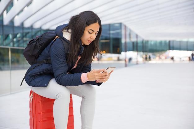 Mulher jovem ocupada séria usando smartphone no aeroporto Foto gratuita
