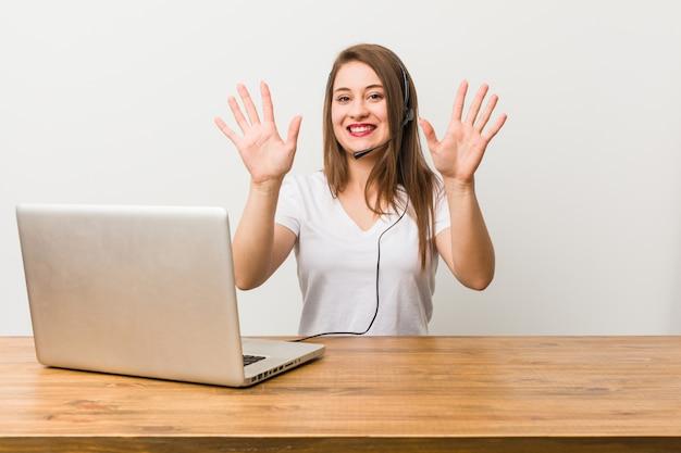Mulher jovem operador de telemarketing mostrando o número dez com as mãos. Foto Premium