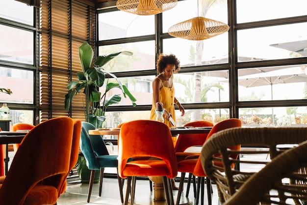 Mulher jovem, organizando, a, tabela, em, a, restaurante Foto gratuita