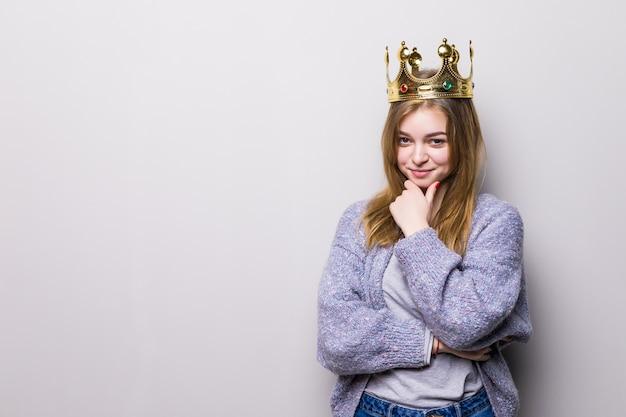 Mulher jovem ou adolescente feliz na coroa da princesa isolada em cinza Foto gratuita