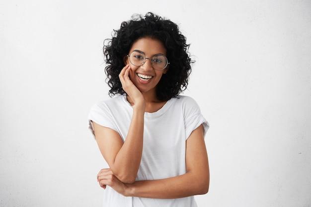 Mulher jovem parda de aparência amigável com cabelos cacheados cacheados e sorrindo alegremente Foto gratuita