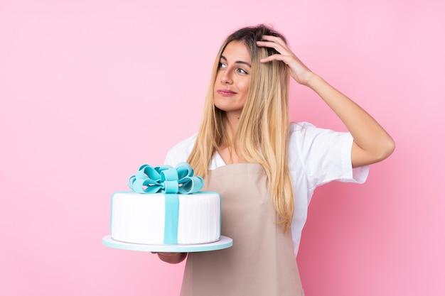 Mulher jovem pastelaria com um bolo grande sobre parede rosa isolada, tendo dúvidas e com a expressão do rosto confuso Foto Premium