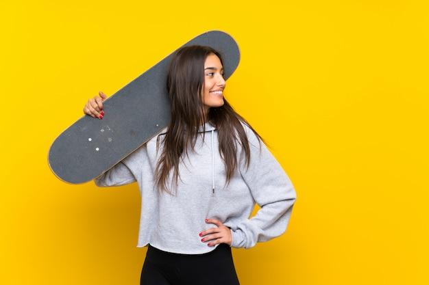 Mulher jovem patinadora sobre parede amarela isolada Foto Premium