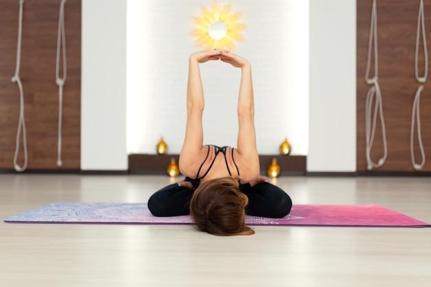 Mulher jovem, prática, ioga, esticar, em, ginásio Foto Premium