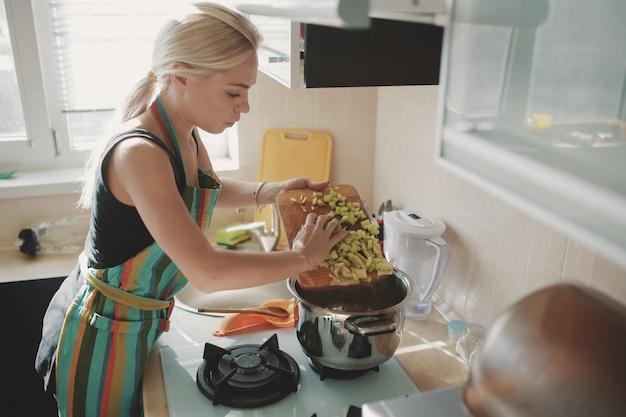 Mulher jovem, preparar, sopa abóbora Foto gratuita