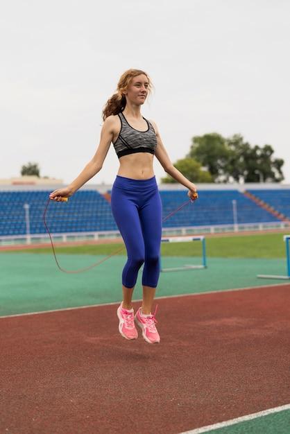 Mulher jovem, pular corda, em, estádio Foto gratuita