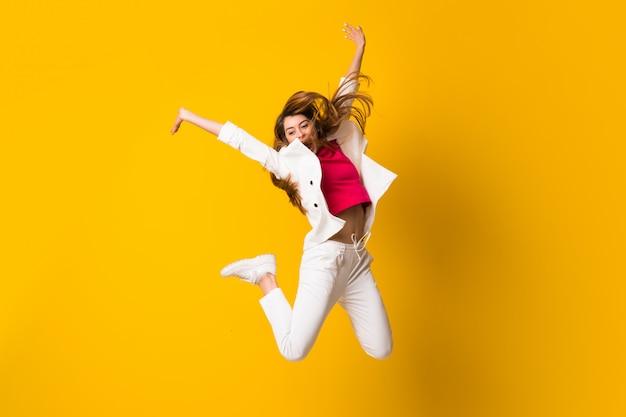 Mulher jovem, pular, isolado, parede amarela Foto Premium