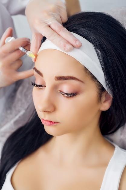Mulher jovem recebendo uma injeção de ácido hialurônico Foto Premium