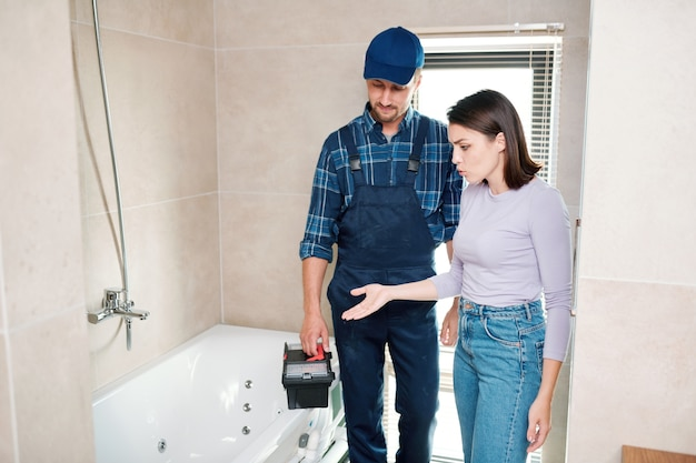 Mulher jovem reclamando com o reparador ou técnico sobre o ralo na banheira ou cano e mostrando a ele onde está o problema Foto Premium