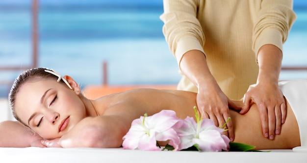 Mulher jovem relaxando em um salão de spa e recebendo massagem corporal Foto gratuita