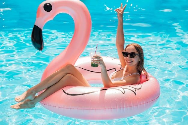 Mulher jovem, relaxante, em, flamingo, anel nadador Foto gratuita