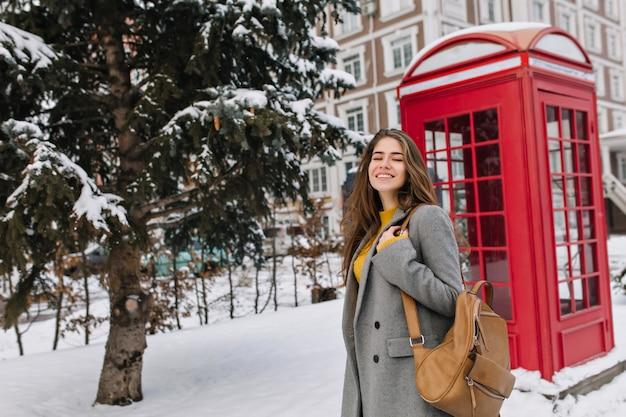 Mulher jovem romântica usa um casaco cinza, andando na rua com a caixa do telefone. retrato ao ar livre de uma mulher maravilhosa com mochila marrom, passar um tempo em winter park, perto de uma cabine telefônica. Foto gratuita