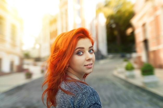 Mulher jovem ruiva assustada, olhando para trás por cima do ombro para a câmera enquanto ela passeia por uma rua urbana deserta | Foto Premium