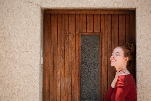 Mulher jovem ruiva posando na frente da porta Foto gratuita
