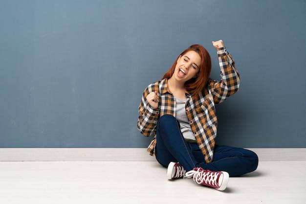 Mulher jovem ruiva sentada no chão comemorando uma vitória Foto Premium