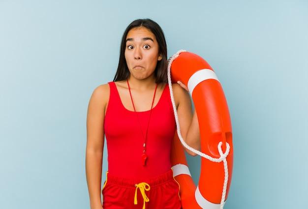 Mulher jovem salva-vidas encolhe os ombros e abre os olhos confusos. Foto Premium