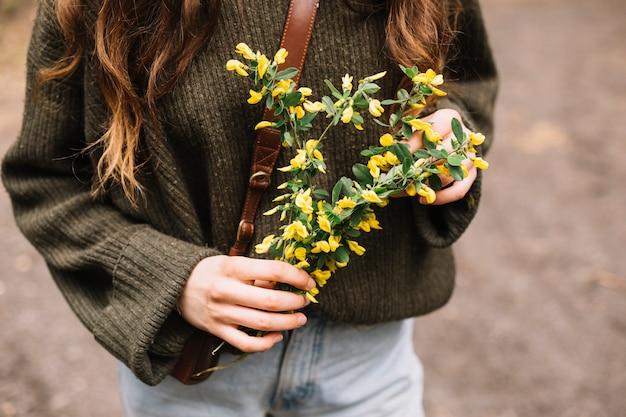 Mulher jovem, segurando, algum, wildflowers Foto gratuita