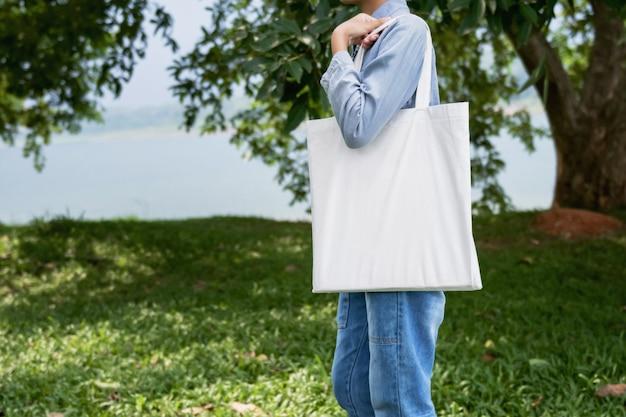 Mulher jovem, segurando, bolsa algodão, em, experiência verde Foto Premium